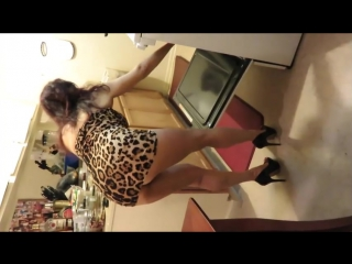 Sexy housewife cooking in leopard mini dress.
