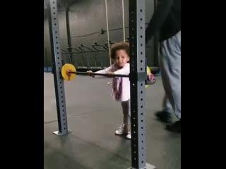 Little girl doing squat