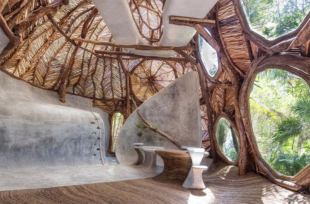 Новая галерея современного искусства IK LAB, расположенная на курорте Azulik в Тулуме (Мексика), выглядит как фантастический дом на дереве с ажурной деревянной крышей и окнами с видом на пальмовые деревья.