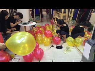 Relaxing footage of Asian girls preparing balloon decorations with some accidental pops